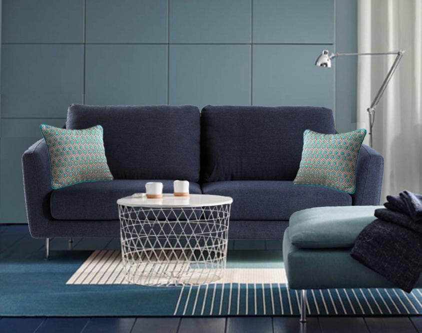 Un exemplaire de notre coussin en velours à motifs gris et turquoise MARQUISES disposé à chaque extrémité de ce canapé bleu indigo