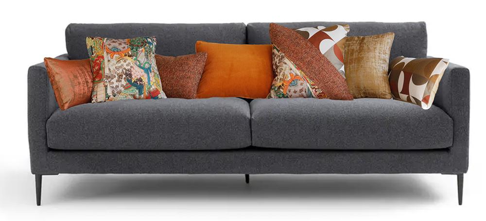 Coussins orange et terracotta sur canapé gris